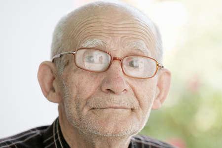 Elderly man in eyeglasses looking to camera outdoor portrait photo