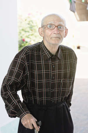 Elderly man in eyeglasses with stick looking to camera outdoors photo
