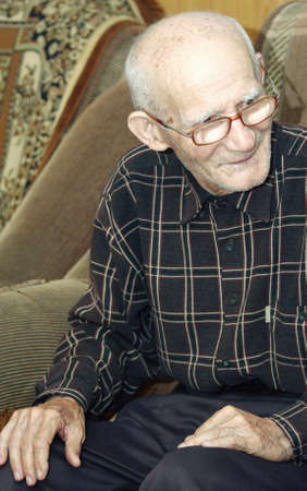 Old man in eyeglasses looking to camera indoor portrait photo