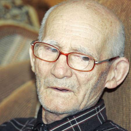Pensive elderly man indoor portrait photo