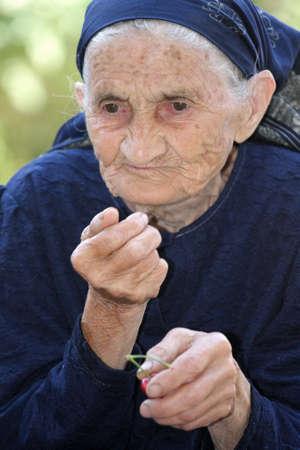 Senior woman eating cherry outdoors looking sideways photo