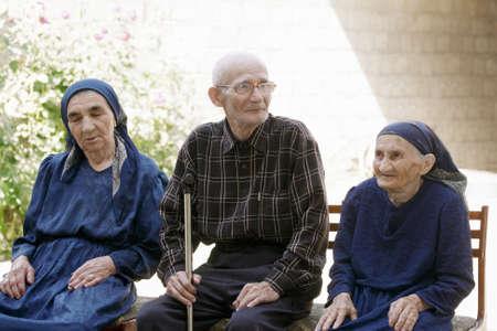 Senior man and women sitting outdoors photo