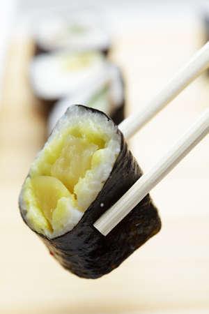 Vegetable sushi roll and chopsticks closeup photo