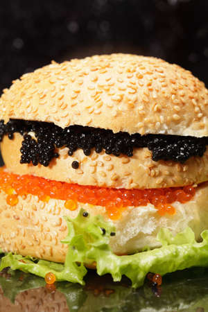 Red and black caviar sandwich on lettuce leaf photo