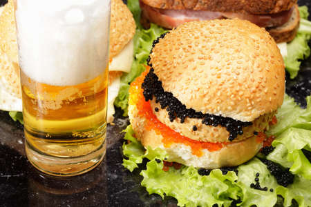 Various sandwiches and pale beer in glass photo