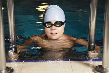 Boy in goggles at swimming pool holding stair rails photo