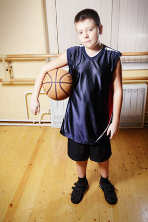 Boy standing with basketball in gym looking to camera photo