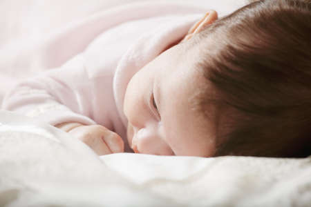 Cute baby in pink laying down on featherbed photo