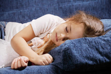 Little cute girl sleeping on blue sofa Stock Photo