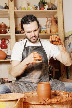 Potter adjusting cutting string in workshop photo