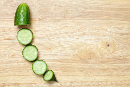 Cucumber slices on cutting board above view photo