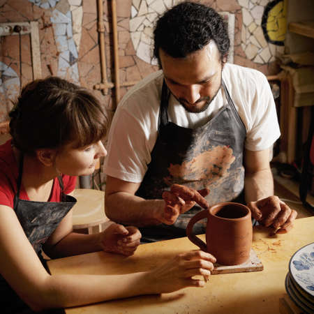 Teacher and student potters at workshop