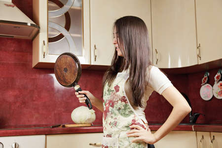 Woman with frying pan in kitchen sideview photo