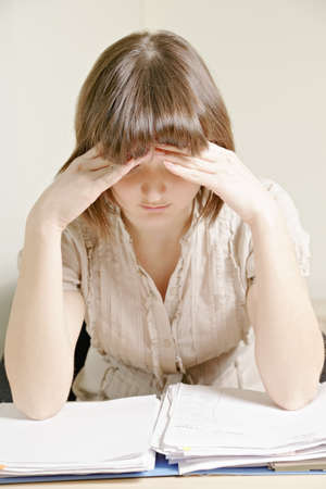 Young woman thinking over papers sitting at desk Stock Photo - 12418738