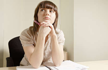 Young pensive woman sitting at desk Stock Photo - 12418736