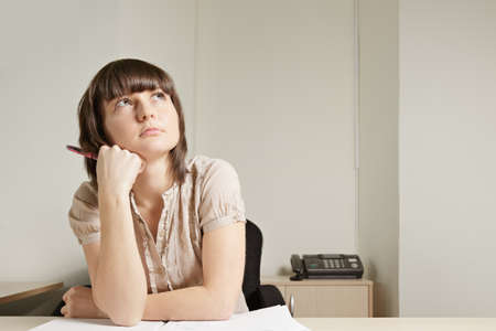 Young brunette woman at desk looking up Stock Photo - 12418723