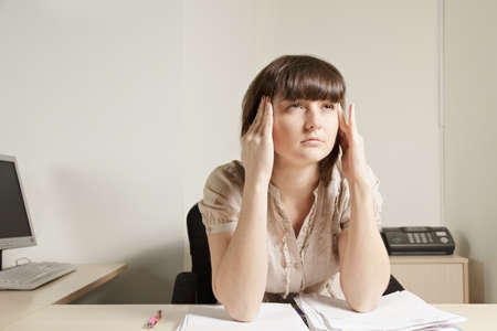 Woman at desk concentrating and pressing temples photo