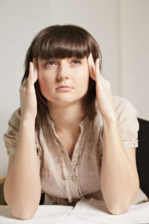 Woman at desk concentrating and pressing temples closeup photo Stock Photo - 12418768
