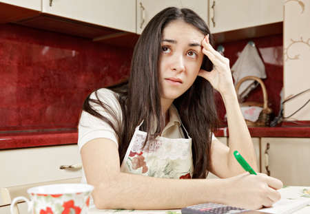 Stressed brunette making calculations sitting at kitchen table Stock Photo - 12669384