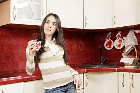 looking sideways: Brunette with cup in kitchen looking sideways Stock Photo