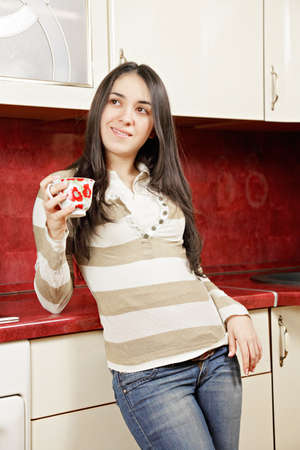 Brunette woman with cup in kitchen looking sideways photo