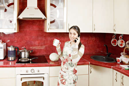 Housewife with cup and phone in kitchen photo