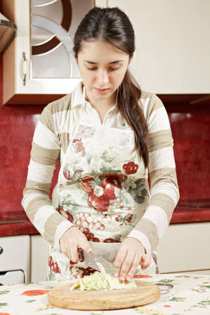 Young brunette cutting cabbage in kitchen photo