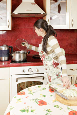 Brunette checking pan while cooking in kitchen photo