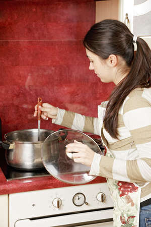 stiring: Brunette housewife stiring soup in saucepan