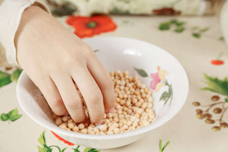 sorting out: Female hand sorting out peas in plate Stock Photo