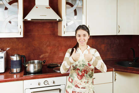 Contented woman gesturing both thumbs up in kitchen photo