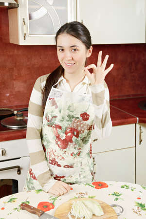 contented: Contented woman gesturing okay sign in kitchen