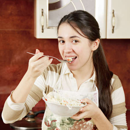 Smiling woman Woman tasting salad in kitchen photo