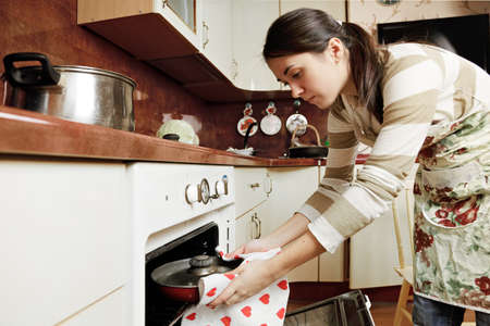 Brunette housewife taking hot frying pan out from oven photo