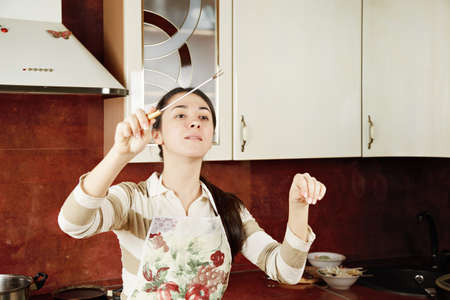 Young woman conducting in kitchen using fork as baton