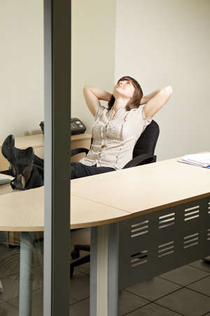 contented: Contented woman in office sitting in chair looking up Stock Photo