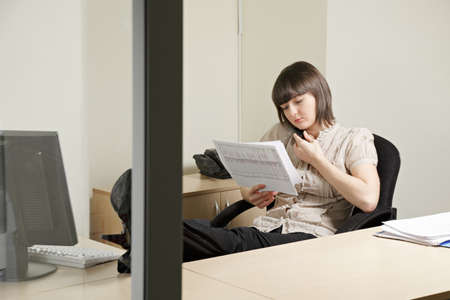 Woman on phone working with documents in office Stock Photo - 12835688