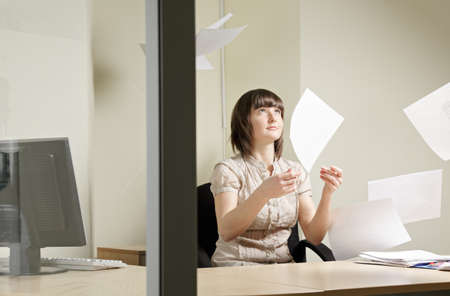 Young woman and flying papers in office Stock Photo