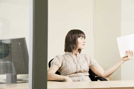 Woman sitting at office desk passing paper sheet Stock Photo - 12835680