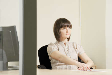 Woman sitting at office desk pointing paper sheet Stock Photo - 12835682