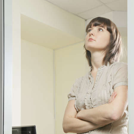 Woman behind office window arms folded Stock Photo - 12835671