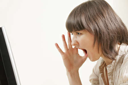 Furious woman shouting at monitor sideview Stock Photo - 12835698