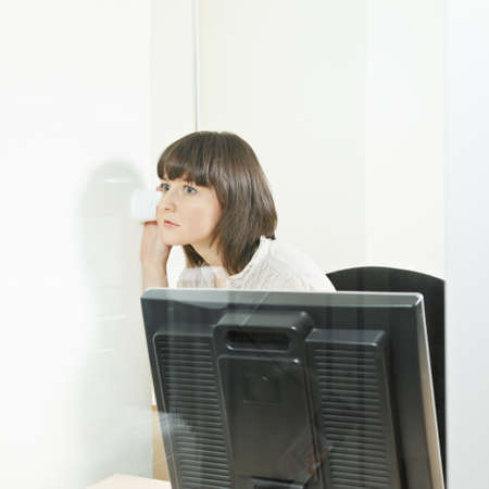 Woman in office listening the wall by empty cup Stock Photo - 12835674