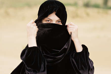 Young woman covering face with hijab headscarf photo