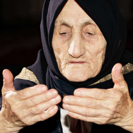 Elderly woman looking at hands while praying photo