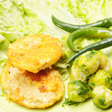 Cutlets with brussels sprout and chili on salad leaf photo