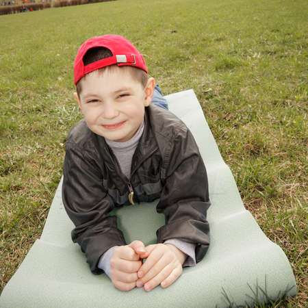 Smiling little boy laying down on mat outdoors Stock Photo - 13220870