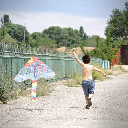 Little kid running with kite outdoors photo