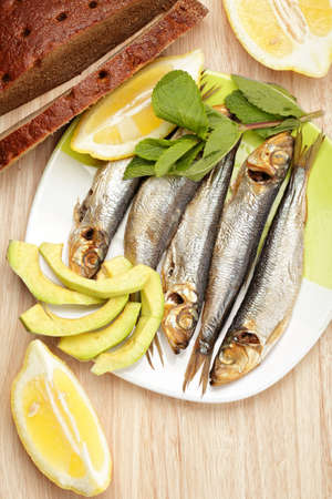 Smoked sprat fish with bread above view photo