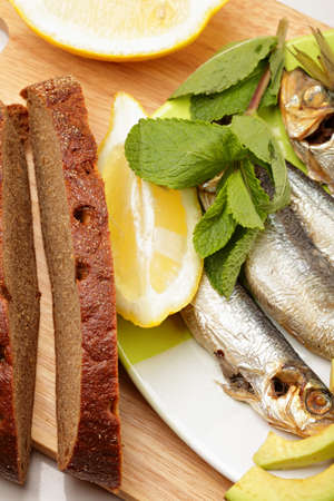sprat: Bread and fish on cutting board closeup Stock Photo